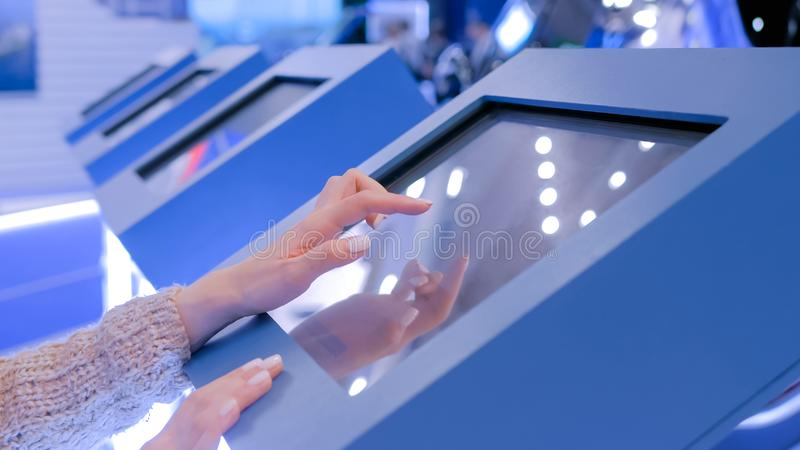 Woman using interactive touchscreen display at technology exhibition. Education and technology concept - woman using interactive touchscreen display of royalty free stock photo