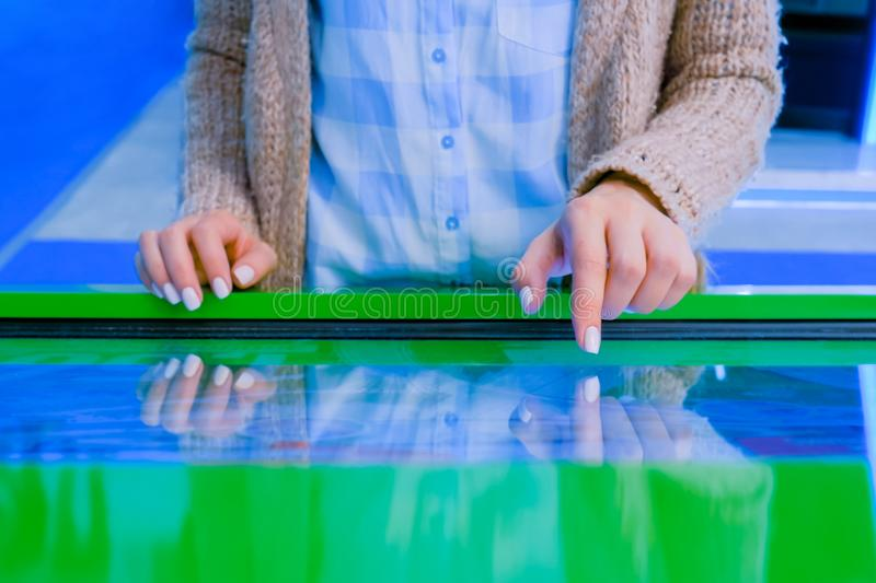 Woman using interactive touchscreen display at technology exhibition. Education and technology concept - woman using interactive touchscreen display of green royalty free stock images