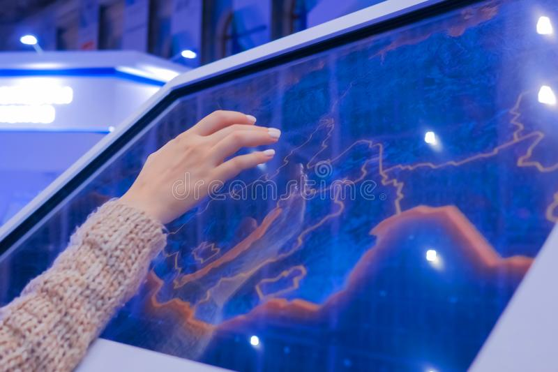 Woman using interactive touchscreen display at technology exhibition. Woman using interactive touchscreen display of electronic multimedia kiosk at technology royalty free stock images