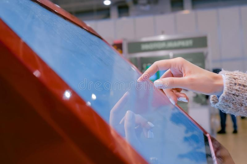 Woman using interactive touchscreen display at technology exhibition. Woman using interactive touchscreen display of red electronic multimedia kiosk at stock images