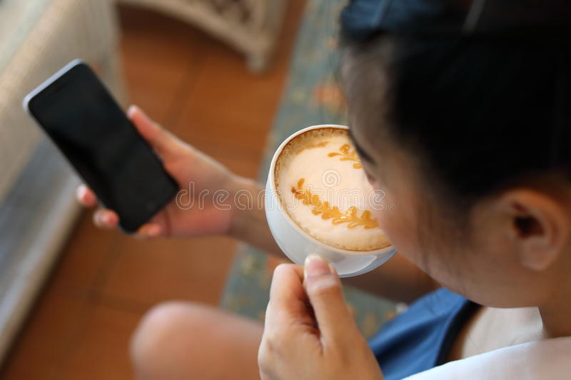 Woman using internet mobile phone technology in cafe coffee stock photo