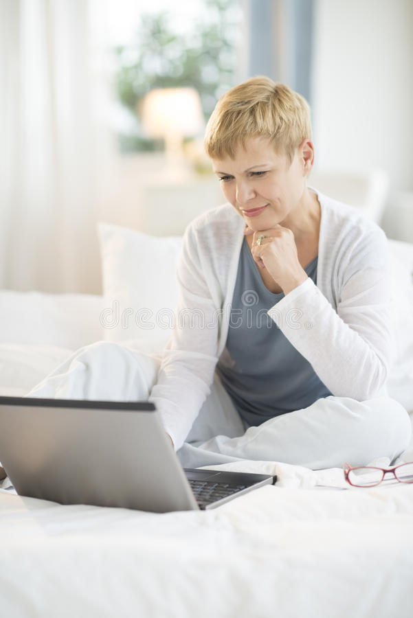 Woman Using Laptop On Bed At Home stock photos