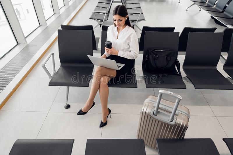 Woman using laptop computer at airport terminal sitting with luggage suitcase for business travel waiting flight royalty free stock photos