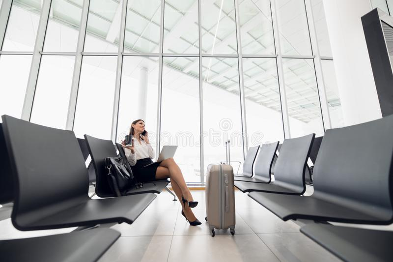 Woman using laptop computer at airport terminal sitting with luggage suitcase for business travel waiting flight. Transport stock photography