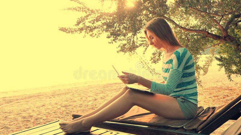 Woman using laptop computer on a beach stock photography