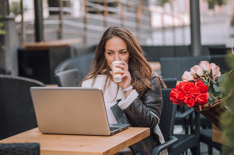 Woman using laptop and drinking coffee in street cafe stock photo