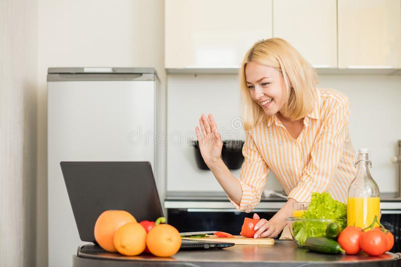 Woman using laptop in the kitchen stock images