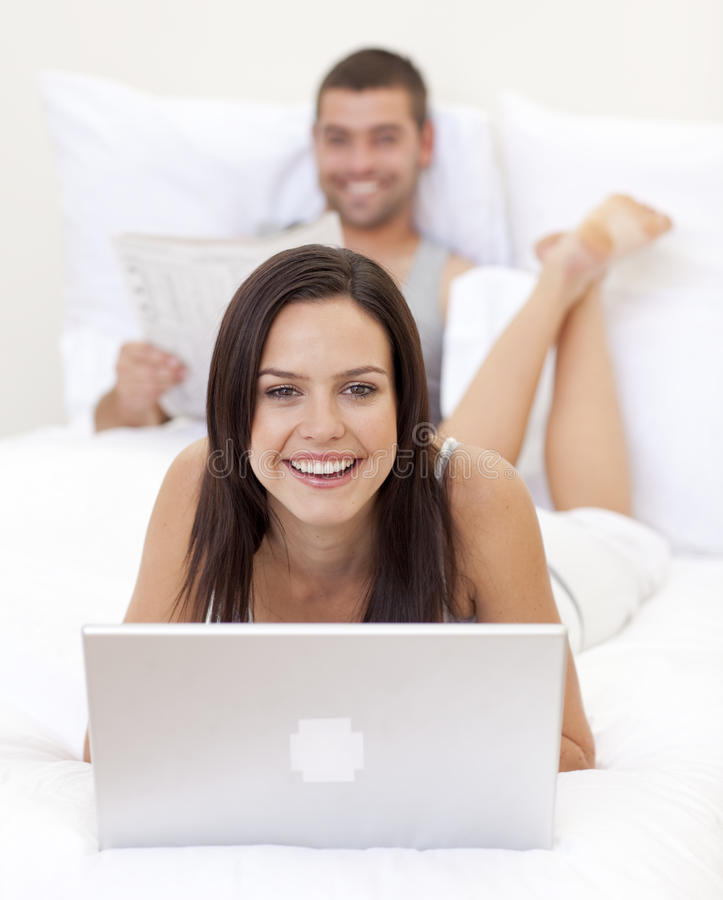 Woman using a laptop and man reading a new royalty free stock image