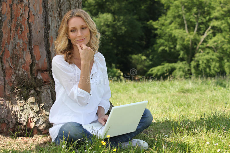 Woman using laptop in park. Blond woman using laptop in park royalty free stock photo