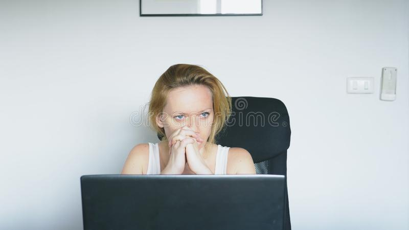 A woman using a laptop sits at the table, feels despair and begins to cry. Human emotions. Internet addiction. A woman using a laptop sits at the table, feels royalty free stock images