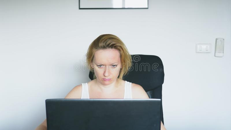 A woman using a laptop sits at the table, feels despair and begins to cry. Human emotions. Internet addiction. A woman using a laptop sits at the table, feels stock photos