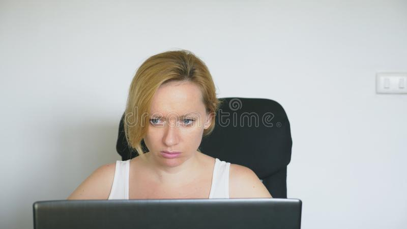 A woman using a laptop sits at the table, feels despair and begins to cry. Human emotions. Internet addiction. A woman using a laptop sits at the table, feels stock photography