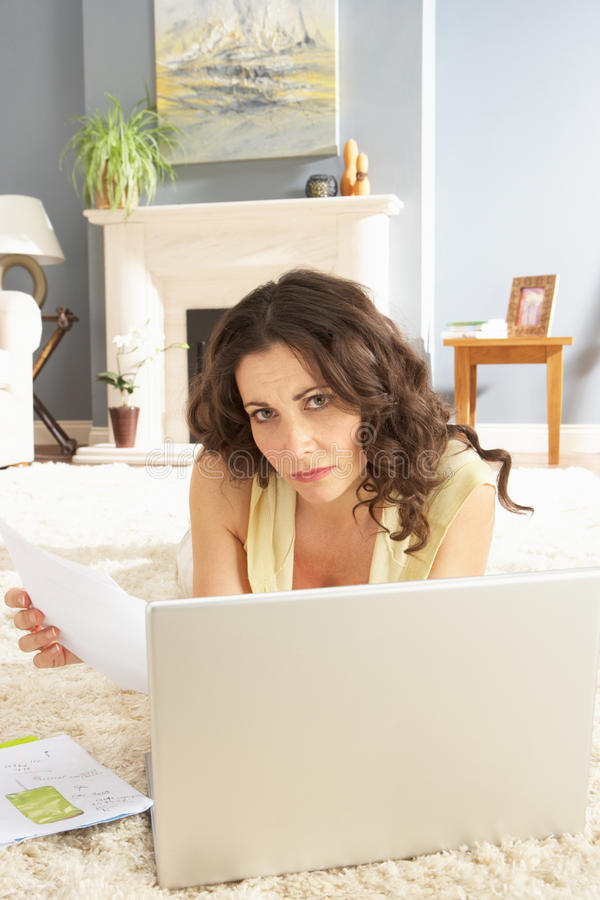 Download Woman Using Laptop To Manage Laying On Rug Stock Photo - Image: 14724018