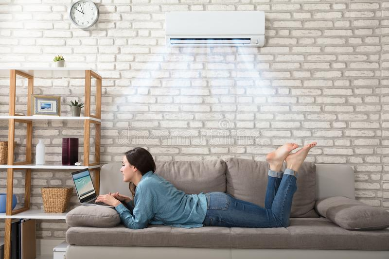 Woman Using Laptop Under The Air Conditioner royalty free stock photo
