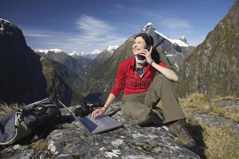 Woman Using Laptop And Walkie Talkie Against Mountains. Young woman using laptop and walkie talkie on boulder against mountains stock images