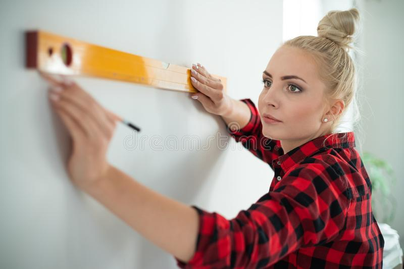 Woman using leveling tool at home royalty free stock image