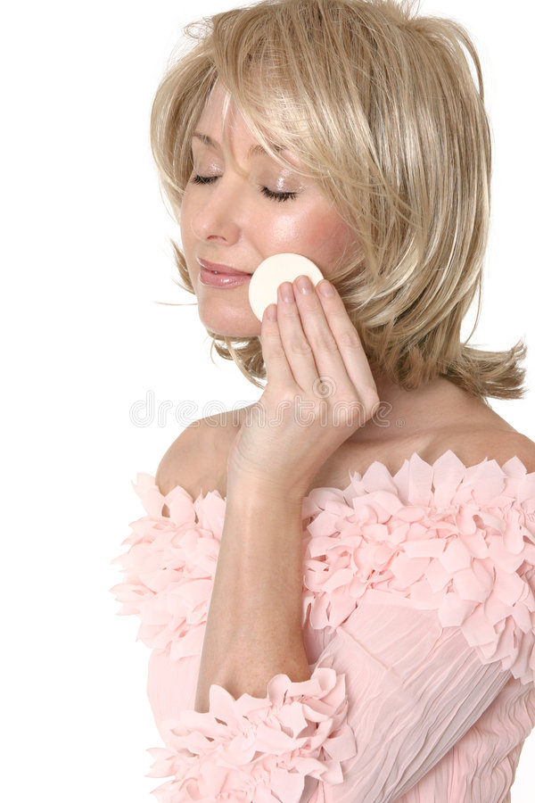 Woman using makeup applicator. A woman removing, applying or touching up makeup to her face royalty free stock photos