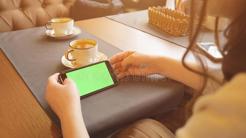 Woman using mobile cell phone with green touch screen in cafe royalty free stock photos