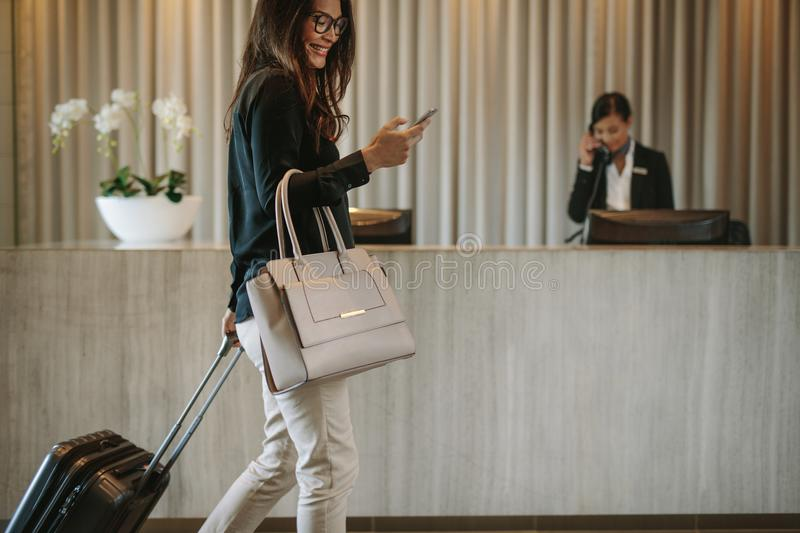 Business traveler in hotel hallway with phone royalty free stock image