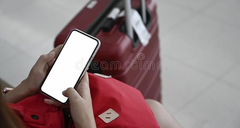 Woman using mobile phone with a red baggage for traveling in terminal airport royalty free stock image
