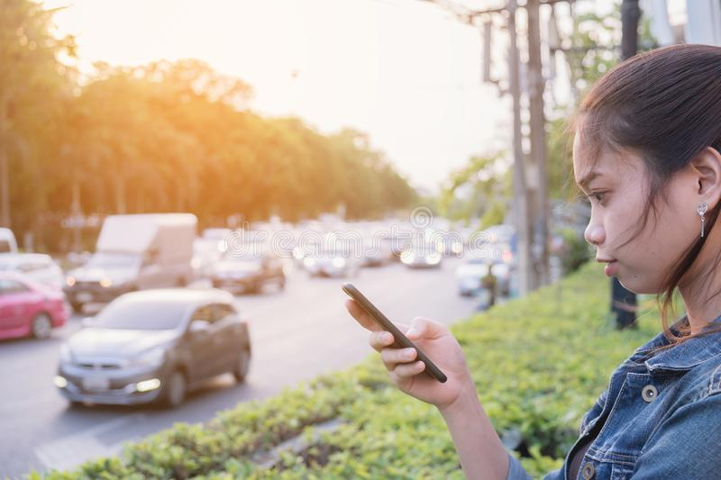 Woman using mobile phone beside road royalty free stock image
