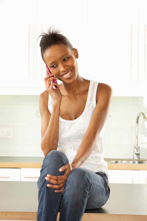 Woman Using Mobile Phone Sitting In Kitchen Stock Photography