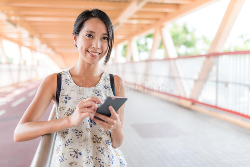 Woman using mobile phone in the street. Asian young woman stock image