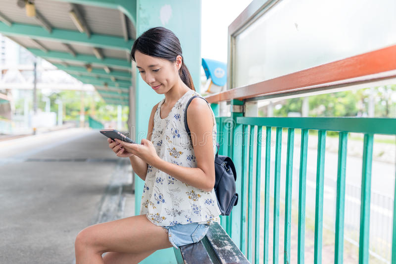 Woman using mobile phone and waiting friends in light rail train royalty free stock photos