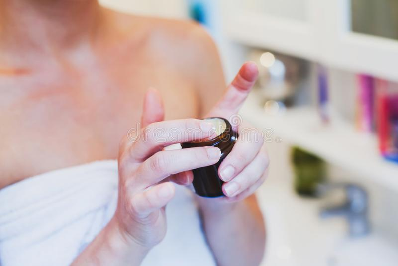 Woman using moisturizing cream for face and body royalty free stock images