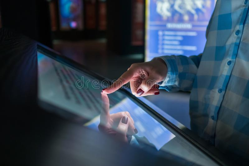 Woman using multimedia touchscreen display of interactive kiosk. Woman using interactive touchscreen display of electronic multimedia terminal at modern museum stock image