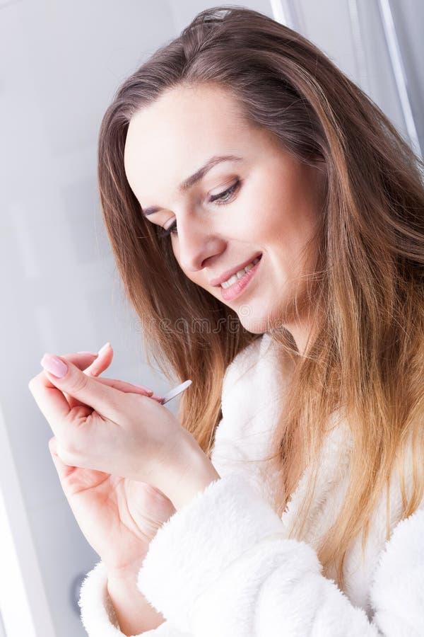 Woman using nail file royalty free stock photo