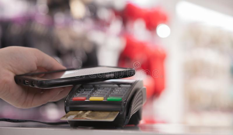 Woman using NFC technology for payment in the shop stock image