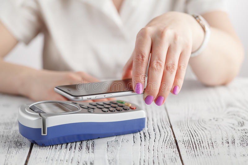 Woman using NFC technology to make payment stock images