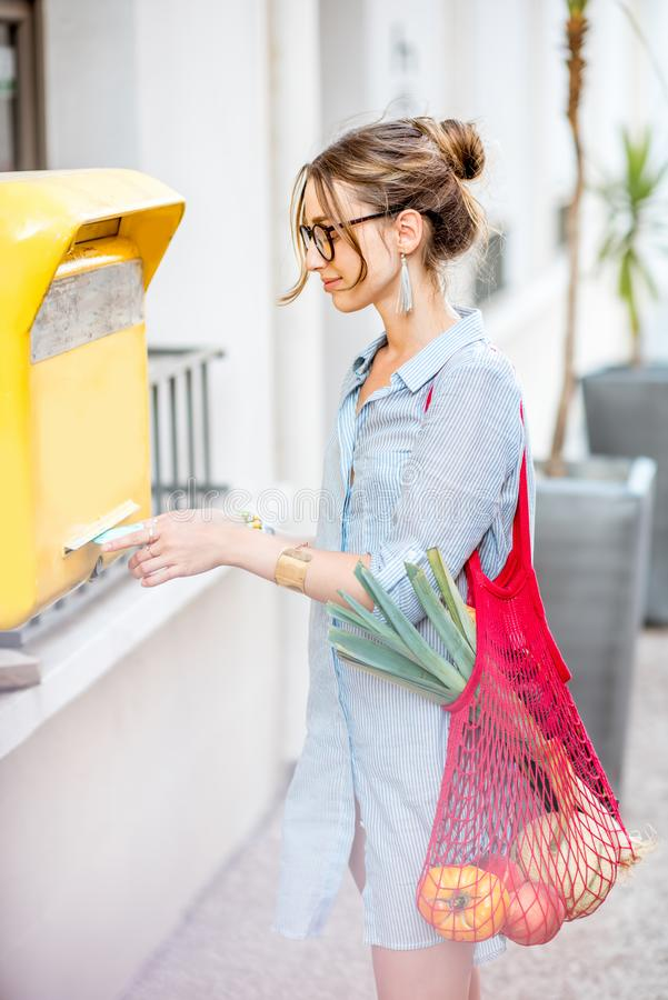 Woman Inserting Envelope In Mailbox Stock Image - Image of