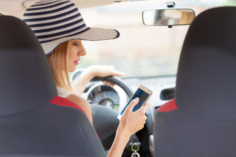 Woman using phone while driving her car stock images