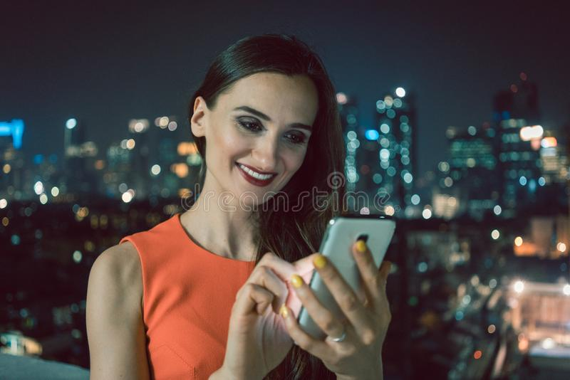 Woman using phone for social media in urban setting royalty free stock images