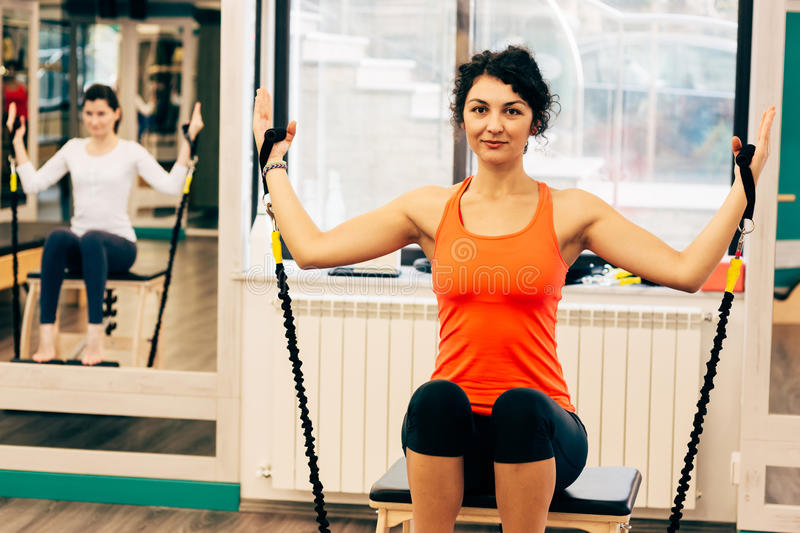 Woman using a pilates chair for exercise royalty free stock images