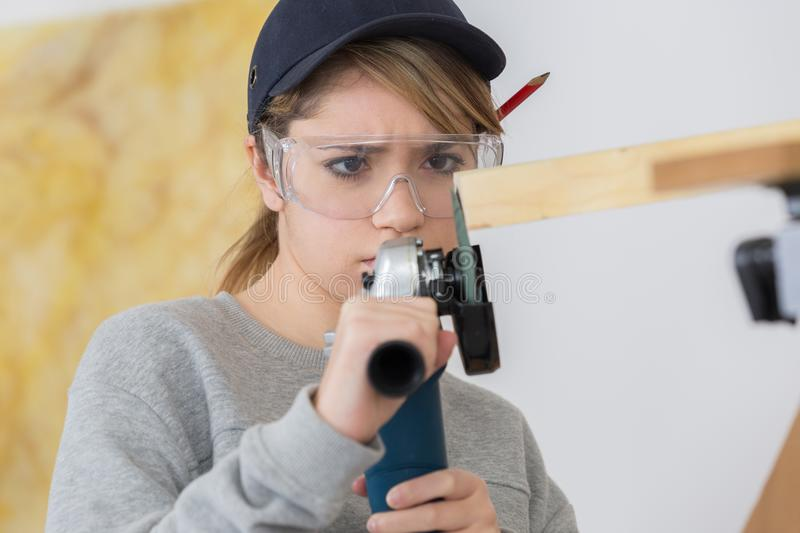 Woman using rotary tool to flatten off end wood. Woman using rotary tool to flatten off end of wood royalty free stock images