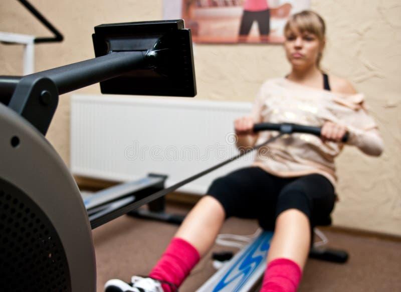 Woman using rowing machine stock photo