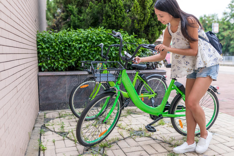 Woman using share bike in the city stock photography