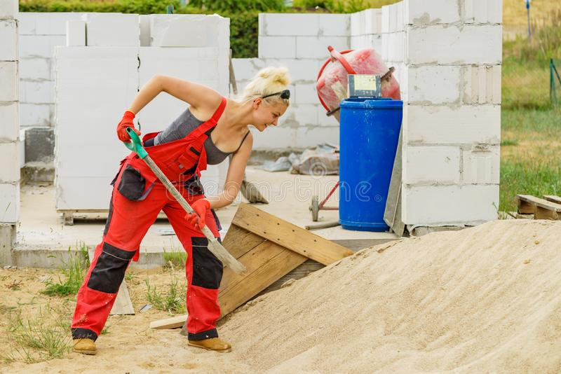 Woman using shovel on constriction site stock photos