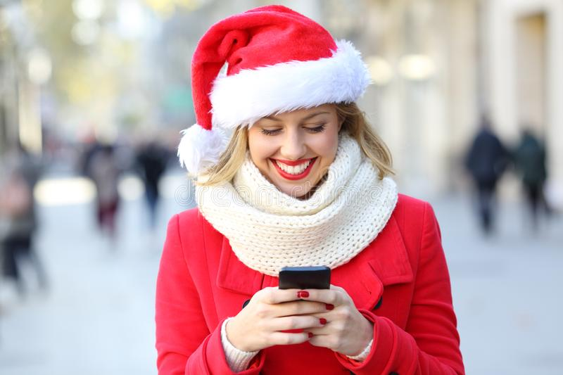 Woman using a smart phone on christmas in the street. Happy woman wearing a santa hat using a smart phone on christmas in the street royalty free stock images