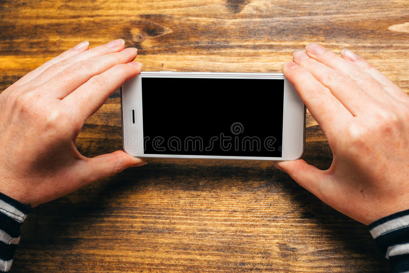 Woman using smart phone in horizontal landscape orientation. For streaming movies or browsing picture gallery, blank screen as copy space stock image
