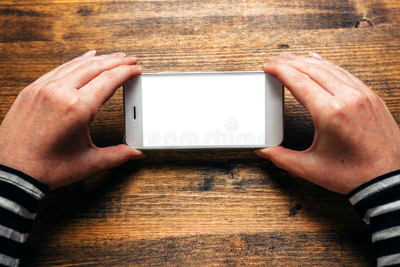 Woman using smart phone in horizontal landscape orientation. For streaming movies or browsing picture gallery, blank screen as copy space royalty free stock image