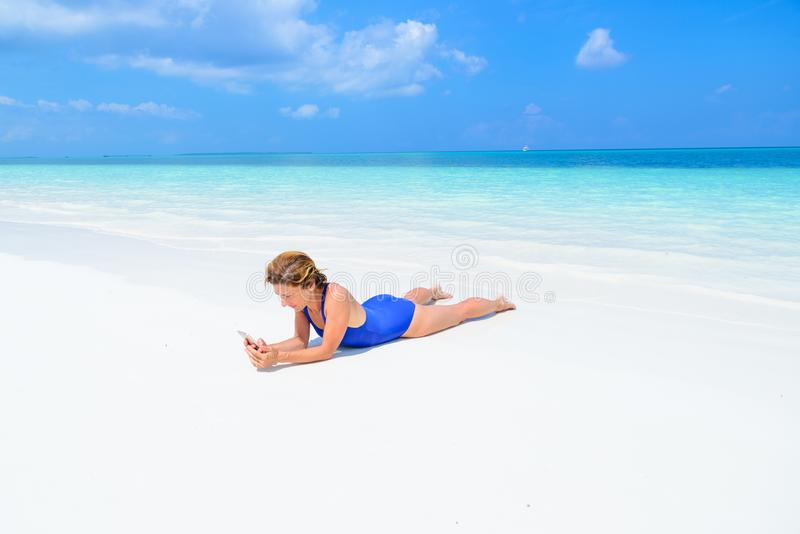 Woman using smart phone relaxing on white sand beach, real people traveling around the world. Indonesia tropical destination, stock photos