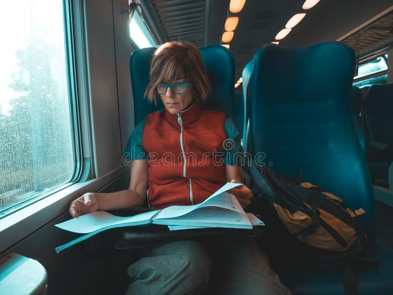 Woman using smart phone sitting traveling by train hand writing on paper. Desaturated cold tone color grading. Working mobility co royalty free stock photo
