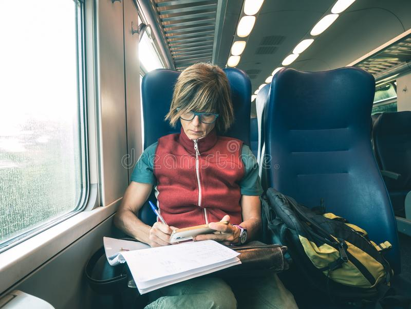 Woman using smart phone sitting traveling by train hand writing on paper. Desaturated cold tone color grading. Working mobility co stock image