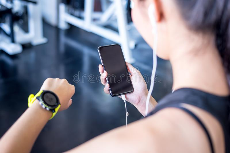 Woman using smart phone tracking with sports watch stock photography