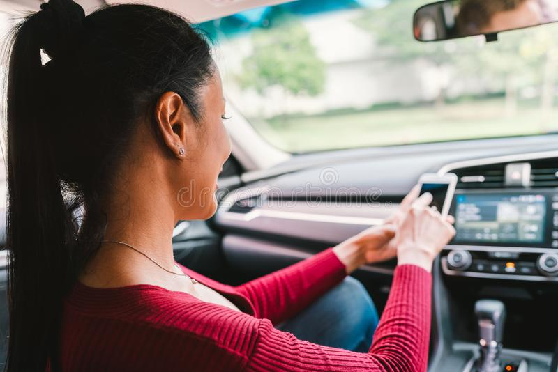 Woman using smartphone app on modern car. Mobile phone application, map navigation device technology, transportation concept royalty free stock photo