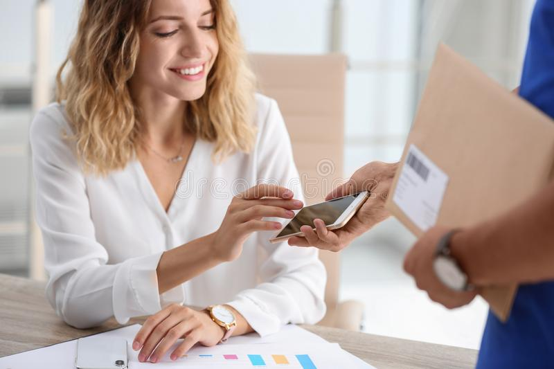 Woman using smartphone app to confirm receipt. Of envelope from courier in office royalty free stock images